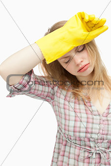 Tired woman wearing cleaning cloves