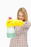 Young woman smiling while holding a spray bottle