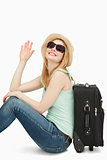 Woman sainsing her hand while sitting near a suitcase