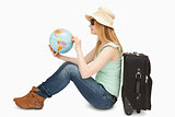 Woman holding a world globe while sitting