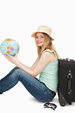 Young woman smiling while holding a world globe