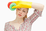 Woman wiping her forehead while holding sponges