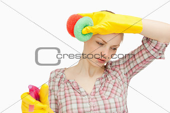 Young woman wiping her forehead while holding sponges