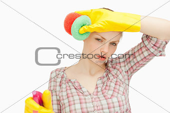 Woman wiping her frown while wearing cleaning gloves