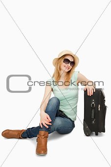 Blonde-haired woman sitting near a suitcase