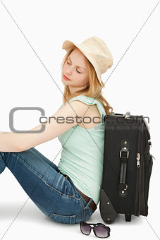 Blonde-haired woman sitting against a suitcase