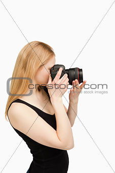 Blonde-haired woman aiming with a camera