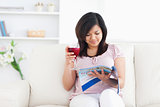 Woman holding a glass of red wine while reading a magazine