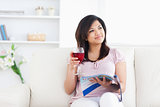 Woman holding a magazine and a glass of red wine