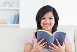 Woman smiling while holding a book