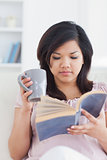 Woman holding a mug while reading a book