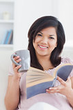 Woman smiling while holding a mug and a book