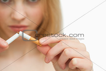 Close up of the hands of a woman breaking a cigarette