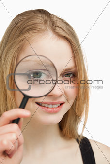 Close up of a woman using a magnifying glass