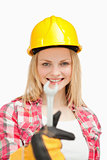 Smiling woman presenting a wrench