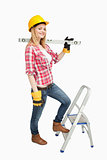 Woman holding a spirit level next to a step ladder