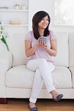 Woman sitting on a sofa while she is smiling