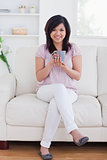 Woman holding a mug while sitting in a couch