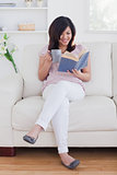 Woman reading a book while sitting on a couch