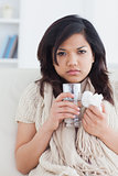 Sick woman holding a tissue and a glass of water