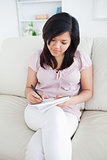 Woman sitting on a sofa while writing in a notebook