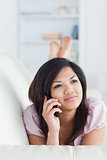 Woman relaxing on a couch while phoning