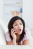 Chocked woman phoning while resting on a couch