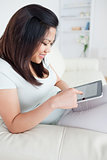 Woman holding a tablet while sitting on a couch