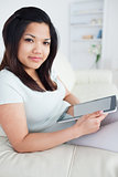 Woman sitting on a couch while holding a tactile tablet