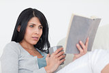 Woman holding a grey mug while reading a book