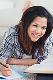 Woman smiling as she lays on the floor and writes on a notebook