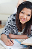 Smiling woman on the floor writing on a notebook