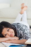 Woman crossing her legs and her arms as she lays on the floor