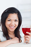 Close-up of a smiling woman holding a glass of red wine