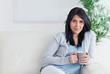 Woman relaxing on a couch while holding a mug