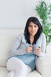 Woman relaxing on a sofa while holding a grey mug