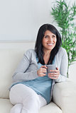 Woman sitting on a couch while holding a grey mug