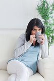 Woman drinking from a grey mug