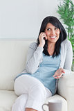 Woman talking on the phone while sitting on a couch