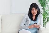 Woman holding a phone while sitting on a couch