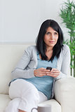 Woman holding a phone while crossing her legs and relaxing on a