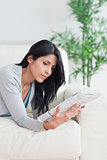 Woman reading a magazine while relaxing on a couch