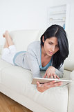 Woman playing with a tactile tablet while laying on a couch