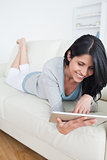 Smiling woman lying on a couch and plays with a tactile tablet
