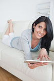 Smiling woman resting on a sofa while playing with a tablet