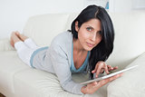 Woman resting on a sofa while touching a tactile tablet