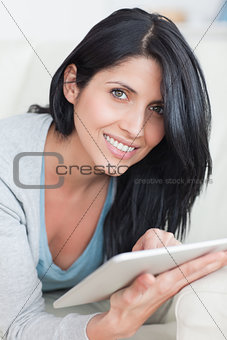 Close up of a smiling woman playing with a tablet