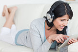 Woman with headphones on while playing with a tablet
