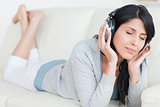 Woman laying on a sofa while wearing headphones