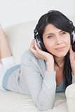 Woman wearing headphones and laying on a couch